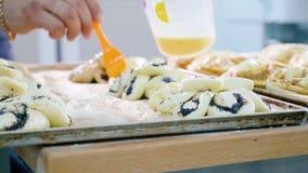 Хлебопек смазывая верхнюю поверхность сладостной выпечки перед входным сигналом в печь стоковая фотография rf