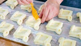 Хлебопек смазывая верхнюю поверхность сладостной выпечки перед входным сигналом в печь стоковая фотография