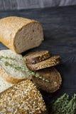 Хлебцы черно-белого хлеба на черной предпосылке доски Натюрморт, захваченный от стороны стоковые фото
