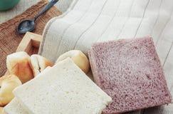 Хлебы и чашки на скатерти Стоковое Изображение RF