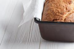 Хлеб банана в лотке с белой пергаментной бумагой на белом деревянном столе конец вверх Хлеб трескает картину Стоковое фото RF