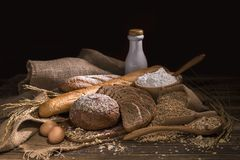 Хлеб всей пшеницы, молоко, мука и ткань кладут в мешки на деревянной таблице стоковые изображения