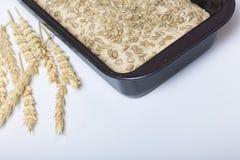 Хлеб выпечки дома Wholemeal тесто лежит в лотке хлеба Семена подсолнуха разбросаны на поверхность теста Затем на стоковые изображения rf