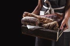 Хлеб в старой деревянной коробке в руках стоковые изображения