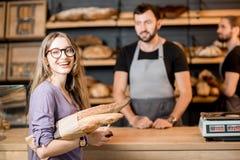 Хлеб женщины покупая в магазине хлебопекарни с продавцами человека стоковое фото