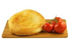 Хлеб и томаты пита на деревянной доске изолированной на белой предпосылке Стоковое Фото