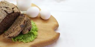 Хлеб Rye с листьями салата, яйцами и стеклом молока на разделочной доске с открытым космосом для текста стоковые фотографии rf