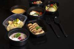 Хлопья и ягоды, суп тыквы с испаренными овощами, салат и экзотический фруктовый салат на черной таблице стоковые фотографии rf