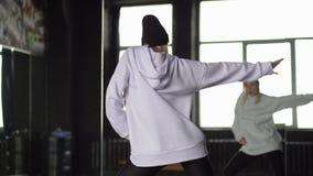 Хмель стильного танца девушки тазобедренный в черно-белых одеждах около зеркала акции видеоматериалы