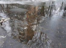 Хмурое раскосное отражение большого дома в коричневой лужице на влажном асфальте, чуть-чуть ветвях дерева, снег плавит Стоковое фото RF