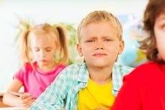 Хмурящся мальчик смотря прямо в классе Стоковое Фото