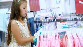 Ходить по магазинам в магазине отдел одежды ` s детей девушка, ребенк, выбирает вещи в магазине Маленькая мод-девушка сток-видео