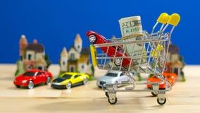 Ходить по магазинам для домов и концепция автомобилей с миниатюрной магазинной тележкаой Стоковые Фото