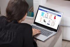 Ходить по магазинам женщины онлайн используя компьтер-книжку стоковое фото