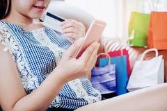 Ходить по магазинам женщины онлайн используя smartphone с наслаждаться кредитной карточки Стоковое Фото