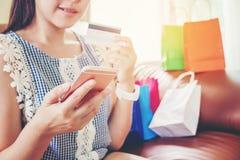 Ходить по магазинам женщины онлайн используя smartphone с наслаждаться кредитной карточки Стоковые Изображения