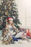 Ходить по магазинам молодой женщины онлайн в уютном интерьере рождества Стоковое Изображение