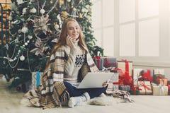 Ходить по магазинам молодой женщины онлайн в уютном интерьере рождества Стоковые Фото
