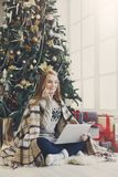 Ходить по магазинам молодой женщины онлайн в уютном интерьере рождества Стоковое Фото