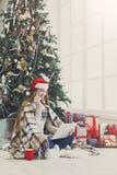 Ходить по магазинам молодой женщины онлайн в уютном интерьере рождества Стоковые Фотографии RF
