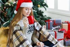 Ходить по магазинам молодой женщины онлайн в уютном интерьере рождества Стоковая Фотография RF