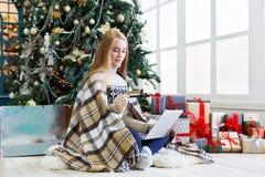 Ходить по магазинам молодой женщины онлайн в уютном интерьере рождества Стоковые Изображения