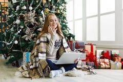 Ходить по магазинам молодой женщины онлайн в уютном интерьере рождества Стоковая Фотография