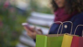 Ходить по магазинам молодой женщины онлайн на smartphone пока сидящ на стенде outdoors видеоматериал