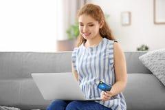 Ходить по магазинам молодой женщины онлайн с кредитной карточкой стоковая фотография rf