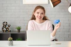 Ходить по магазинам молодой женщины онлайн с кредитной карточкой стоковая фотография