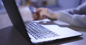 Ходить по магазинам онлайн на портативном компьютере дома в вечере, payin стоковые фото