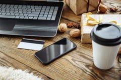 Ходить по магазинам онлайн с кредитной карточкой на праздник рождества Компьтер-книжка, smartphone и подарки на деревянном столе Стоковое Изображение
