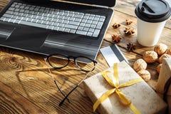 Ходить по магазинам онлайн с кредитной карточкой на праздник рождества Компьтер-книжка с подарками на деревянном столе Стоковое Изображение