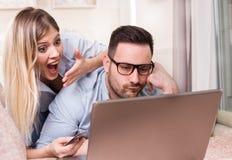 Ходить по магазинам пар онлайн дома Стоковые Изображения RF
