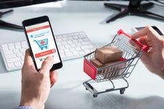 Ходить по магазинам персоны онлайн на мобильном телефоне стоковое фото