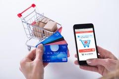 Ходить по магазинам персоны онлайн с кредитными карточками на мобильном телефоне стоковая фотография