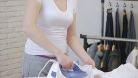 Ходы белая рубашка и танцы домохозяйки женщины с утюгом в ее руках видеоматериал