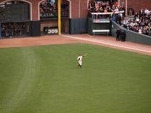ходы ross игрока в дальней части поля шарика cody для того чтобы поднять теплое Стоковые Фотографии RF