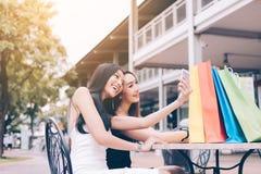 Ходя по магазинам азиатские девушки сидя на вне моле и использовании умных Стоковые Фото