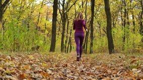 Ход замедленного движения - бегун женщины jogging на пути леса осени Тренировка подходящего женского следа спортсмена модели фитн