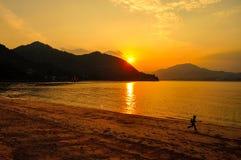 Ход мальчика на пляже с заходящим солнцем на заднем плане стоковые фотографии rf