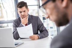 Хозяйничайте анализировать документы с коллегой близко мимо на деловой встрече Стоковое Изображение RF