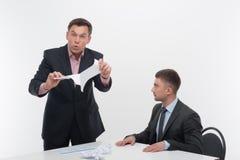 Хозяйничайте сердитое при молодой работник сидя на столе Стоковые Фото