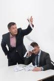 Хозяйничайте сердитое при молодой работник сидя на столе Стоковая Фотография RF