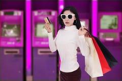Хозяйственная сумка женщины holdking и деньги разделять от кредитной карточки на ATM стоковое изображение rf