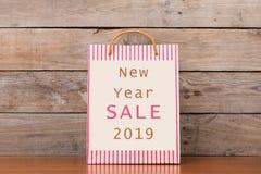 """Хозяйственная сумка картона с текстом """"продажей 2019 Нового Года """" стоковое изображение"""