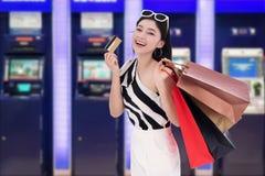 Хозяйственная сумка счастливой женщины holdking и деньги разделять от кредитной карточки на ATM стоковые изображения rf