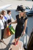 Хозяйственные сумки нося женщины пока всходящ на борт Стоковое фото RF