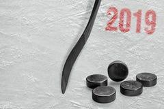 Хоккейная клюшка и шайбы на льде Стоковые Фотографии RF