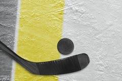 Хоккейная клюшка, шайба и часть арены льда с черными и желтыми линиями стоковая фотография